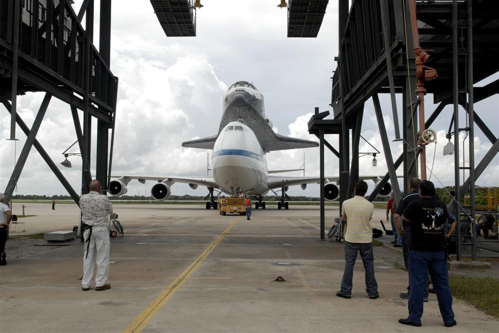 Space shuttle & carrier plane guided into removal structure